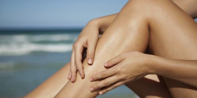 Woman rubbing legs, low section