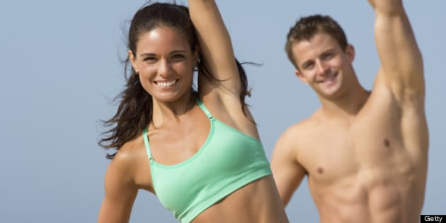 fit couple in sports wear stretching and exercising on the beach