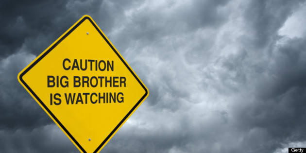 A caution sign in front of storm clouds warning of 'Big Brother is Watching.'