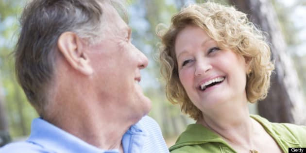 Happy senior couple laughing together on park bench