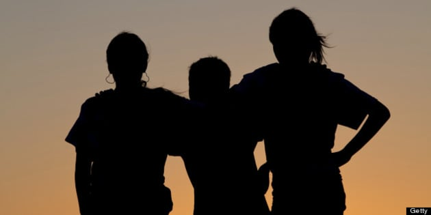 A silhouette of three children bonding at sunset. Affection. Love. Relationships. Friendship.
