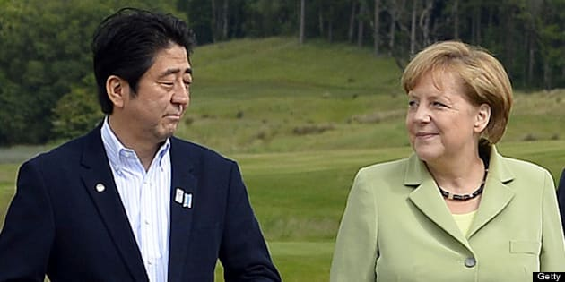 G8 leaders Japan's Prime Minister Shinzo Abe (L) Germany's Chancellor Angela Merkel (C) and Russia's President Vladimir Putin, pose on the podium for the family photograph on the second day of the G8 summit at the Lough Erne resort near Enniskillen in Northern Ireland on June 18, 2013. Russia and the US agreed at the G8 summit to push for Syria peace talks, but Presidents Vladimir Putin and Barack Obama made clear their deep differences over the conflict. AFP Photo/Jewel SAMAD        (Photo credit should read JEWEL SAMAD/AFP/Getty Images)