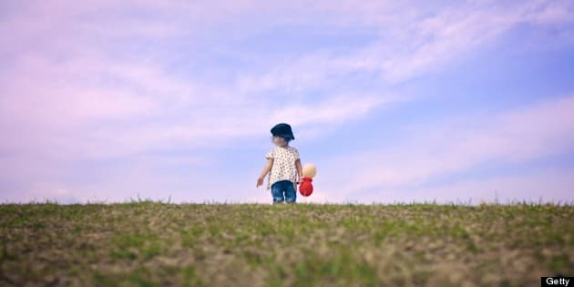 Toddler girl holding balloons on top of grassy hill against backdrop of blue sky.