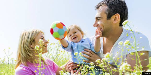 Parents enjoying with their cute son in the nature.
