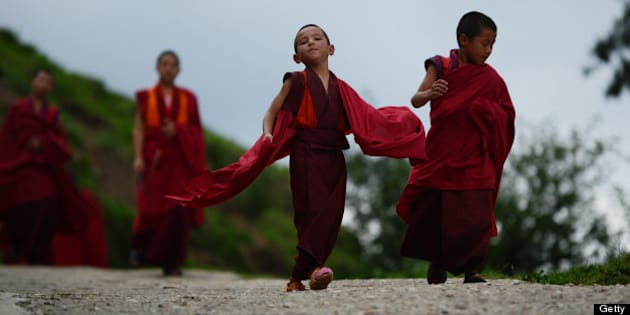 This image is part of of a photo package on children going to school around the world and it shows six-year-old monk apprentice Tandi Dorji (C) as he walks to breakfast at a monastery in Thimpu, the capital of  the Kingdom of Bhutan on June 3, 2013. Dorji is the youngest monk at the Buddhist monastery that overlooks the city and where over 200 monks learn among other things, about meditation, chants, holy scripture and about performing rituals honouring various bodhisattvas which are those being who have generated a spontaneous wish to attain Buddahahood for the benefit of all sentient beings. Dorji came to the monastery when he was five and was initially dropped off by his grandfather who lives with Dorji's mother in a remote village in eastern Bhutan.  AFP PHOTO/Roberto SCHMIDT        (Photo credit should read ROBERTO SCHMIDT/AFP/Getty Images)