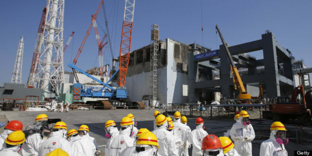 Members of the media and Tokyo Electric Power Co. (Tepco) employees, wearing protective suits and masks, visit the No. 4 reactor building, center, and the construction of a storage unit for melted fuel rods, right, at the company's Fukushima Dai-Ichi nuclear power plant in Okuma, Fukushima Prefecture, Japan, on Wednesday, March 6, 2013. Tepco's Fukushima Dai-Ichi plant had three reactor core meltdowns after it was hit by an earthquake and tsunami on March 11, 2011. Photographer: Issei Kato/Pool via Bloomberg