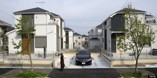 A man walks past residential properties in Yokohama, Kanagawa Prefecture, Japan, on Wednesday, April 10, 2013. Nationwide land prices on average fell 1.8 percent as of Jan. 1, compared with a 2.6 percent decline a year earlier, the Ministry of Land, Infrastructure, Transport and Tourism said in a report on March 21. Photographer: Akio Kon/Bloomberg via Getty Images