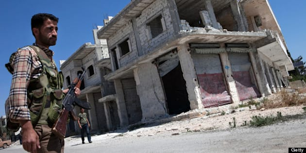 A Rebel walks in front of a destroyed building in the village of Al-Rami, near the town of Ariha, in the northwestern Syrian province of Idlib, on June 22, 2013. World powers supporting Syria's rebels decided to take 'secret steps' to change the balance on the battlefield, after the United States and others called for increasing military aid to insurgents. AFP PHOTO / DANIEL LEAL-OLIVAS        (Photo credit should read DANIEL LEAL-OLIVAS/AFP/Getty Images)
