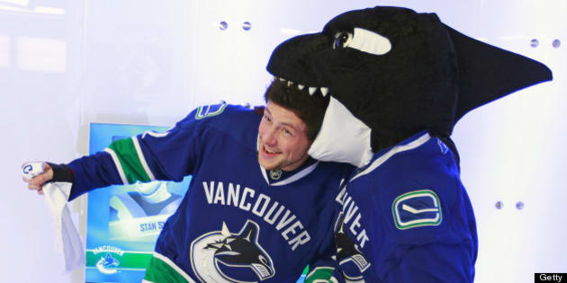 VANCOUVER, CANADA - DECEMBER 26:  Cory Monteith, a Canadian actor from the television show 'Glee', jokes around with Vancouver Canucks mascot Fin before their game against the Edmonton Oilers at Rogers Arena on December 26, 2010 in Vancouver, British Columbia, Canada. (Photo by Jeff Vinnick/NHLI via Getty Images)