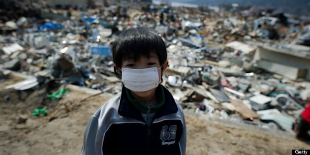 A boy stands among destroyed houses and debris in the tsunami-damaged town of Yamada, in Iwate prefecture, on March 25, 2011. Two weeks after a giant quake struck and sent a massive tsunami crashing into the Pacific coast, the death toll from Japan's worst post-war disaster topped 10,000 and there was scant hope for 17,500 others still missing. AFP PHOTO/ Nicolas ASFOURI (Photo credit should read NICOLAS ASFOURI/AFP/Getty Images)