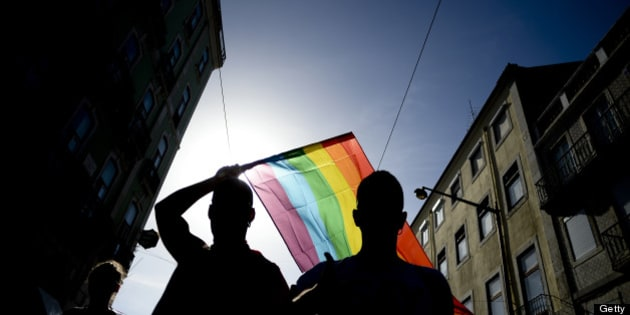 A man waves a rainbow flag as he takes part in the Gay Pride Parade in Lisbon on June 22, 2013. AFP PHOTO/ PATRICIA DE MELO MOREIRA        (Photo credit should read PATRICIA DE MELO MOREIRA/AFP/Getty Images)