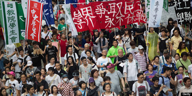 HONG KONG - JULY 01:  Thousands of protesters march on July 1, 2013 in Hong Kong. Thousands of protesters march calling for universal suffrage and chanting slogans against Hong Kong Chief Executive C Y Leung when Typhoon Signal No. 3 is hoisted. Hong Kong Special Administrative Region Establishment Day is celebrated every July 1st, in Hong Kong since 1997. (Photo by Lam Yik Fei/Getty Images)