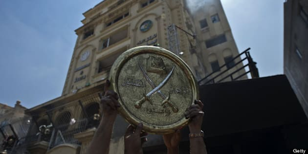 Egyptians hold a plaque of the Muslim Brotherhood emblem which was removed from the party's burnt headquarters in the Moqattam district of Cairo on July 1, 2013 after it was set ablaze by opposition demonstrators overnight. Egypt's opposition gave Islamist Mohamed Morsi a day to quit or face civil disobedience after deadly protests demanded the country's first democratically elected president step down after just a year in office. AFP PHOTO / KHALED DESOUKI        (Photo credit should read KHALED DESOUKI/AFP/Getty Images)