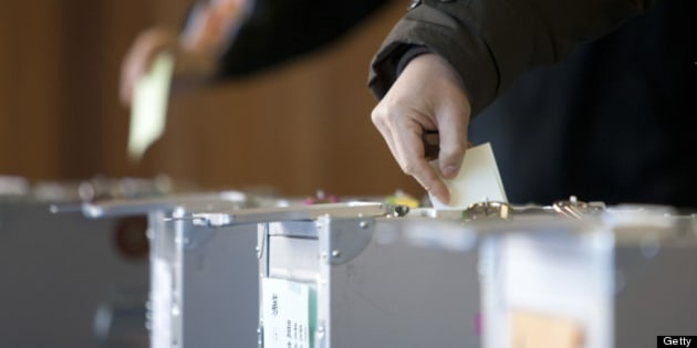 Voters cast their ballots at a polling station in Tokyo, Japan, on Sunday, Dec. 16, 2012. Japanese voters go to the polls today for parliamentary elections that will likely topple the ruling Democratic Party of Japan, and give the nation its seventh leader in six years. Photographer: Tomohiro Ohsumi/Bloomberg via Getty Images