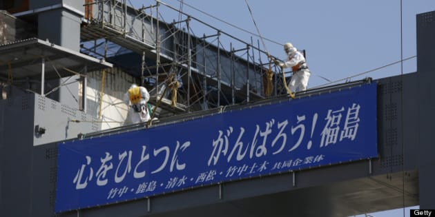 Workers wearing protective suits and masks stand on the construction site of a storage unit for melted fuel rods next to the No. 4 reactor building at Tokyo Electric Power Co.'s (Tepco) Fukushima Dai-Ichi nuclear power plant in Okuma, Fukushima Prefecture, Japan, on Wednesday, March 6, 2013. Tepco's Fukushima Dai-Ichi plant had three reactor core meltdowns after it was hit by an earthquake and tsunami on March 11, 2011. Photographer: Issei Kato/Pool via Bloomberg