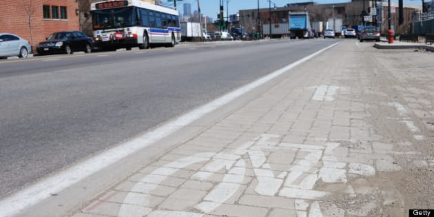 Smog eating paving stones form a bicycle lane on Blue Island Ave, which Chicago city officials havce dubbed the greenest street in America, are seen on April 1, 2013 in Chicago, Illinois. The $14 million project to reshape two miles of Blue Island and Cermak also includes streetlights lights that run on solar and wind power, sidewalks made with recycled concrete, and shrub-filled 'bioswales' to keep storm water out of overtaxed sewers.AFP PHOTO/MIRA OBERMAN          (Photo credit should read MIRA OBERMAN/AFP/Getty Images)