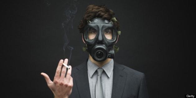 Businessman Wearing Gas Mask and Smoking Cigarette