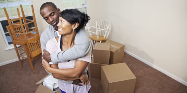 Moving house.  African American mid adult couple (30s) moving into new home.
