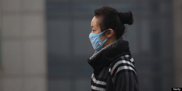 A woman wears a mask as she walks on a street in Beijing, China, on Friday, March 15, 2013. China's new premier promised to crack down on corruption and clean up pollution, acknowledging the need to tackle two issues that have stoked public anger toward the country's leaders. Photographer: Tomohiro Ohsumi/Bloomberg via Getty Images