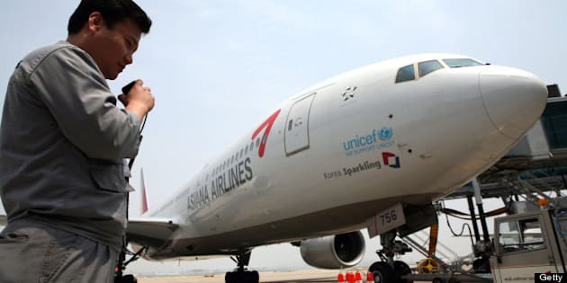 SOUTH KOREA - MAY 22:  An airport ground staff member uses his radio as he stands near an Asiana Airlines Inc. passenger jet at Incheon International Airport, in Incheon, South Korea, on Thursday, May 22, 2008. Korean Air Lines Co., South Korea's largest carrier, fell to the lowest in a year in Seoul trading on concern record oil prices may result in losses. Asiana Airlines Inc., the country's second-biggest airline, lost 3.5 percent to 5,720 won.  (Photo by Jean Chung/Bloomberg via Getty Images)
