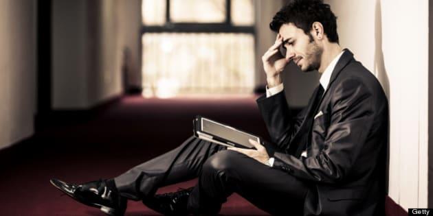 Frustrated Businessman reading bad news on his digital tablet. Dark scene.