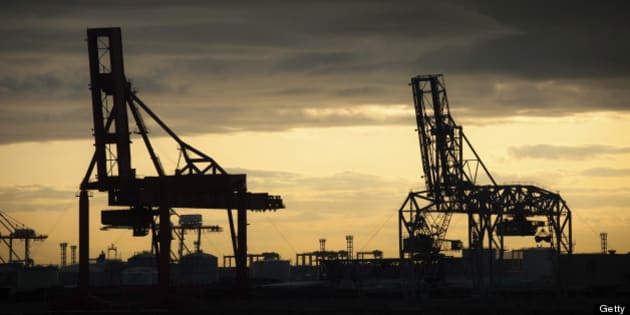Cargo cranes are silhouetted against a golden sky at the Osaka harbor and shipping complex in Japan.