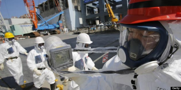 A radiation monitor reads 114.00 microsieverts per hour as members of the media and Tokyo Electric Power Co. (Tepco) employees, wearing protective suits and masks, visit the No. 4 reactor building, background center, and the construction of a storage unit for melted fuel rods, background right, at the company's Fukushima Dai-Ichi nuclear power plant in Okuma, Fukushima Prefecture, Japan, on Wednesday, March 6, 2013. Tepco's Fukushima Dai-Ichi plant had three reactor core meltdowns after it was hit by an earthquake and tsunami on March 11, 2011. Photographer: Issei Kato/Pool via Bloomberg
