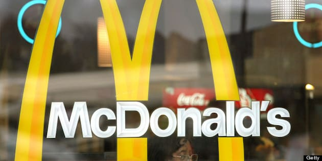 WILLOWBROOK, IL - NOVEMBER 11:  (FILE PHOTO)  A patron is seen through a window displaying McDonald's golden arches as she eats her meal November 11, 2002 in Willowbrook, Illinois. The Oak Brook, Illinois-based company has announced that it will restructure its operations in four countries and close in three countries, shutting down approximately 175 underperforming restaurants in about 10 other countries and eliminating 400-600 positions to control costs and reallocate resources. McDonald's Corporation announced its first quarterly net loss ever January 23, 2003 in Oak Brook, Illinois. The $343.8 million loss for the last three months of 2002 shows the company's charges and write-offs. The fast-food chain said that it would close about 600 restaurants this year, including 400 traditional McDonald's.  (Photo by Tim Boyle/Getty Images)