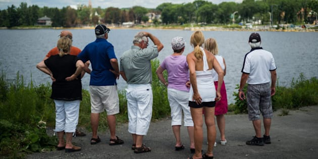 LAC-MEGANTIC, CANADA - JULY 14:  People look out toward the 'red zone' crash site, on July 14, 2013 in Lac-Megantic, Quebec, Canada. A train derailed and exploded into a massive fire that flattened dozens of buildings in the town's historic district, leaving 60 people dead or missing in the early morning hours of July 6.  (Photo by Ian Willms/Getty Images)