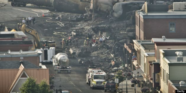 LAC-MEGANTIC QC - JULY 8: Search teams carry a large white bag out of the rubble in the town centre of Lac-MÈgantic during their search for the dead Monday evening.  40 more are missing after a train derailment caused a massive explosion early Saturday morning.        (Lucas Oleniuk/Toronto Star via Getty Images)