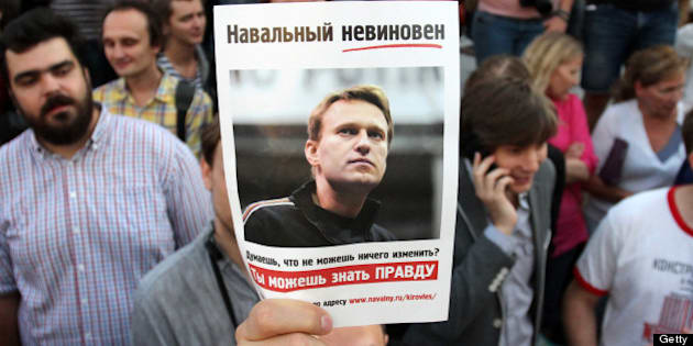 A protester holds a portrait of opposition leader Alexei Navalny, sentenced to five years in a penal colony after finding him guilty of embezzlement in a timber deal, on July 18, 2013 during a demonstration in central Moscow. Judge Sergei Blinov said he found Navalny guilty of colluding to steal money in a timber deal while acting as an unpaid advisor to the local government in the northern Kirov region.    AFP PHOTO / IVAN NOVIKOV        (Photo credit should read IVAN NOVIKOV/AFP/Getty Images)