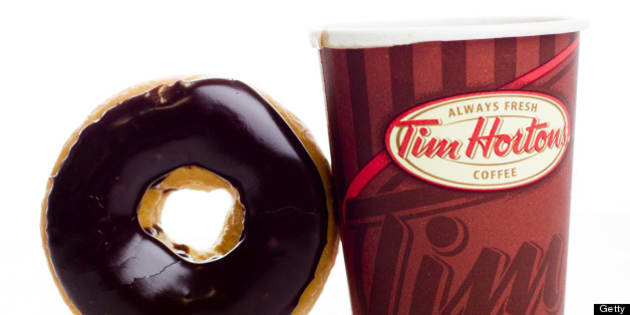 A cup of Tim Hortons Inc. coffee and doughnut are arranged for a photograph in Toronto, Ontario, Canada, on Wednesday, Aug. 3, 2011. Tim Hortons Inc. is a chain of franchise fast food restaurants that serve coffee drinks, tea, soups, sandwiches, donuts, bagels, and pastries. Photographer: Brent Lewin/Bloomberg via Getty Images