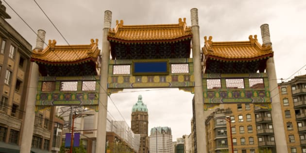 Pender Street leading through the Millennium Gate in Vancouver Chinatown with the Sun Tower in the background.