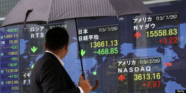 A pedestrian holding an umbrella looks at an electronic stock board displaying the closing figure of the Nikkei 225 Stock Average, top center, outside a securities firm in Tokyo, Japan, on Monday, July 29, 2013. Japan shares fell, with the Topix index capping the biggest two-day loss in two months, as exporters slumped on a stronger yen and Mitsubishi UFJ Financial Group Inc. and Sumitomo Mitsui Financial Group Inc. sparked banks' biggest back-to-back retreat since May. Photographer: Tomohiro Ohsumi/Bloomberg via Getty Images