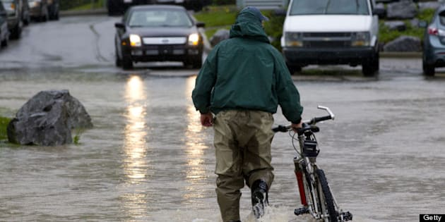 CANMORE, CANADA - JUNE 21:   A man pushes his bicycle through the floodwater June 21, 2013 in Canmore, Alberta, Canada.  Widespread flooding caused by torrential rains washed out bridges and roads prompting the evacuation of thousnds.  (Photo by John Gibson/Getty Images)