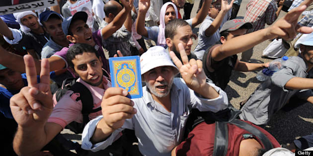 An Egyptian supporter of deposed president Mohamed Morsi raises a Koran flashing the sign of victory during a demonstration against the government in al-Nasr street in Cairo on July 30, 2013. EU foreign policy chief Catherine Ashton met Egypt's ousted president on July 30, 2013, saying he was 'well,' but the country's political crisis seemed no closer to resolution despite her efforts.    AFP PHOTO/FAYEZ NURELDINE        (Photo credit should read FAYEZ NURELDINE/AFP/Getty Images)