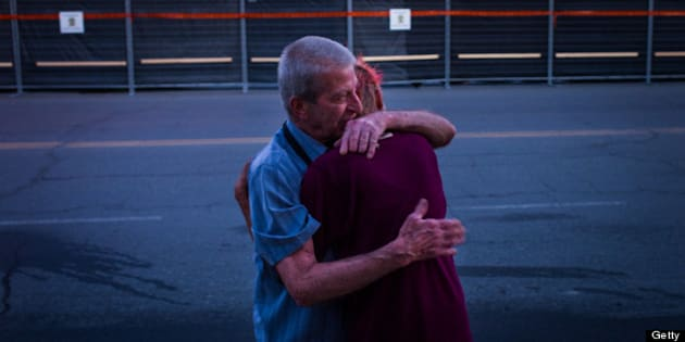LAC-MEGANTIC, CANADA - JULY 14:  Marcel Larrivee (L) comforts Patricia Landry after the pair first witnessed the aftermath of the destruction on July 14, 2013 in Lac-Megantic, Quebec, Canada. A train derailed and exploded into a massive fire that flattened dozens of buildings in the town's historic district, leaving 60 people dead or missing in the early morning hours of July 6.  (Photo by Ian Willms/Getty Images)