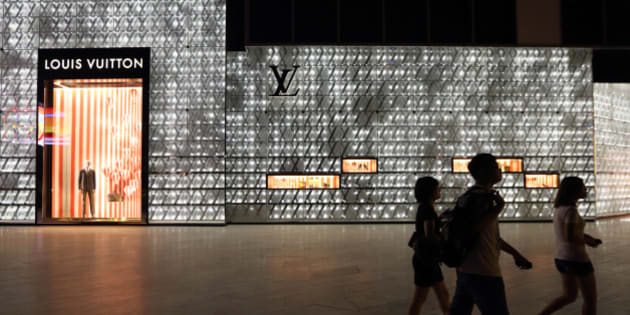 Pedestrians walk past a Louis Vuitton store, operated by LVMH Moet Hennessy Louis Vuitton SA, as it stands illuminated at night in Shanghai, China, on Tuesday, July 2, 2013. Banks including Goldman Sachs Group Inc. have pared their growth projections for China this year to 7.4 percent, below the government's 7.5 percent goal disclosed at the March conference at which Li Keqiang became premier. Photographer: Tomohiro Ohsumi/Bloomberg via Getty Images