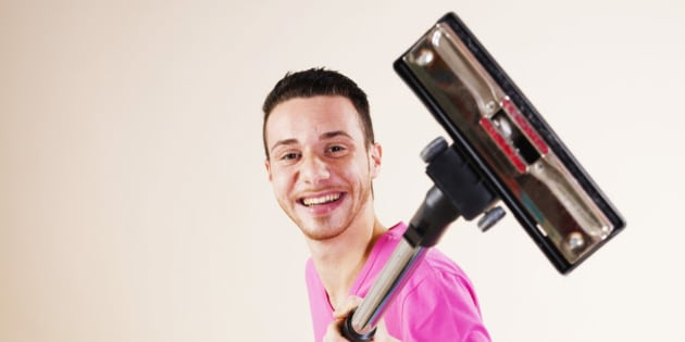 Happy young man with vacuum cleaner