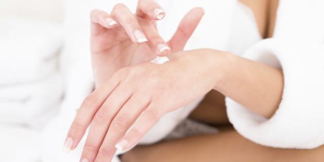 Woman sitting wearing towel moisturizing hand