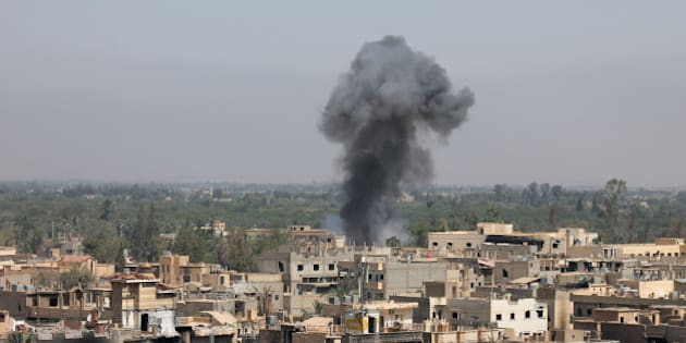 TOPSHOTS - Smoke rises from buildings in Syria's eastern town of Deir Ezzor on August 13, 2013 following an airstrike by government forces. Syrian opposition activists, including National Coalition members, have drawn up a transitional roadmap including a call for national reconciliation and justice for 'all of Syria's victims,' a statement said.     TOPSHOTS / AFP PHOTO / ABO SHUJA        (Photo credit should read ABO SHUJA/AFP/Getty Images)