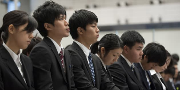 University students take notes as they attend a job fair hosted by Recruit Co. at Makuhari Messe in Chiba City, Japan, on Sunday, Dec. 11, 2011. Japan's economy grew less than the government's initial estimate last quarter as companies reduced investment on concern overseas demand was stalling. Photographer: Akio Kon/Bloomberg via Getty Images