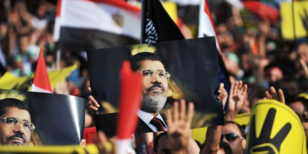 A protestor holds up a poster of ousted Egyptian President Mohamed Morsi during a demonstration condemning the recent deadly military crackdown on pro-Morsi protesters in Cairo on August 17, 2013, at New Mosque in Istanbul. Turkey branded the deadly crackdown in Egypt on protesters loyal to ousted president Mohamed Morsi today as 'unacceptable' and called on the international community to act immediately to halt the 'massacre'. AFP PHOTO/OZAN KOSE        (Photo credit should read OZAN KOSE/AFP/Getty Images)