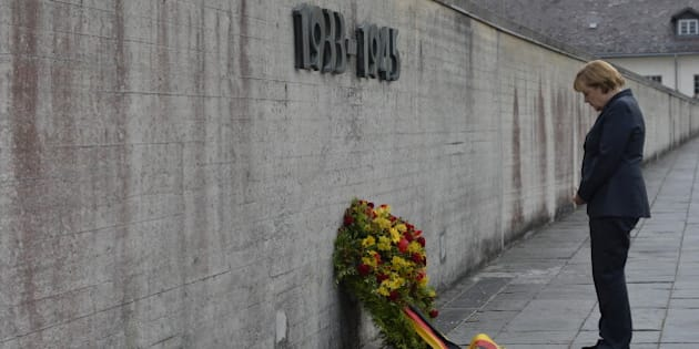 German Chancellor Angela Merkel pays respect during a wreath-laying ceremony at the wall of the Concentration Camp Memorial in Dachau, southern Germany on August 20, 2013. More than 200,000 Jews, gays, Roma, political opponents, the disabled and prisoners of war were imprisoned in Dachau during World War II. Merkel became the first German Chancellor to visit the camp but critics slammed her decision to include the stop on an election campaign swing.  AFP PHOTO / GUENTER SCHIFFMANN        (Photo credit should read GUENTER SCHIFFMANN/AFP/Getty Images)
