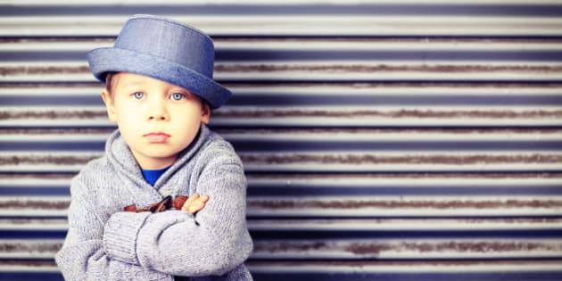 A cute, four year old little boy wearing a fedora style hat and sweater, sitting with his arms crossed. Kids fashion, back to school concept. Similar images.