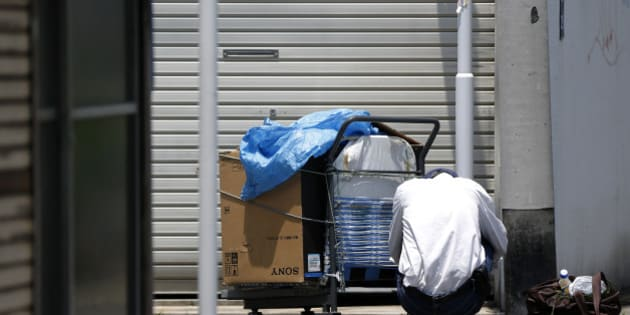 An elderly man squats next to a cart and a bag on a street in Tokyo, Japan, on Monday, July 8, 2013. The number of Japanese seniors living alone will rise 54 percent to 7.17 million in 2030 from 4.66 million in 2010, according to the National Institute of Population and Social Security Research, set up by the Ministry of Health, Labour and Welfare. To manage the costs stemming from the aging society, the government aims to push back the pension age to 65 from 60 in stages through 2025. Photographer: Kiyoshi Ota/Bloomberg via Getty Images