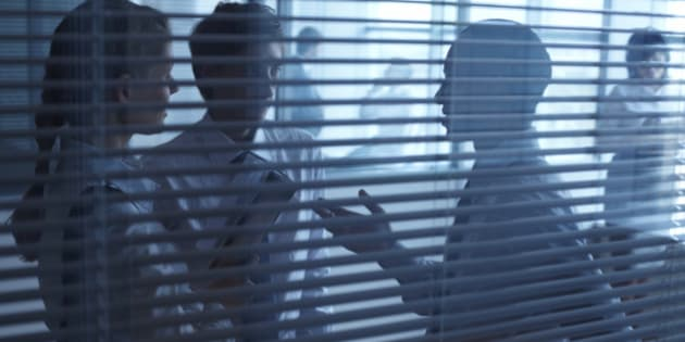 Three businesspeople talking behind the blinds