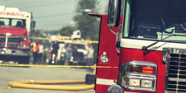 Firetrucks, caution tape, fire hoses and bystanders on the scene of a devastating house fire.