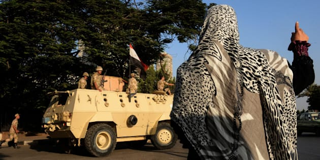 An Egyptian woman waves to soldiers on top of an armoured vehicle guarding the entrance of a military hospital where former Egyptian president Hosni Mubarak was transferred after his release from prison on August 22, 2013 in Cairo.  Mubarak was sent to the military hospital after his release from prison after he was cleared for conditional release while standing trial, an interior ministry general told AFP. He will be held under house arrest at the Cairo hospital on the orders of the prime minister, who has been granted the power to order arrests during the current state of emergency. AFP PHOTO/MARWAN NAAMANI        (Photo credit should read MARWAN NAAMANI/AFP/Getty Images)