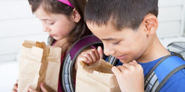 Siblings 6/7 digging in their school lunch bag